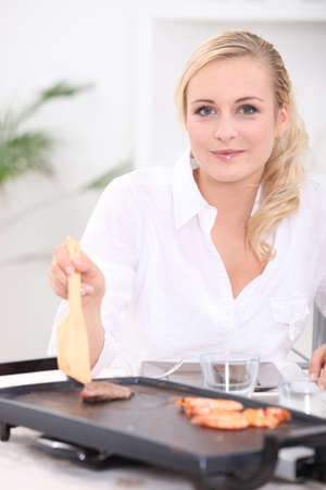 tantalizing: Woman cooking seafood and meat on a plancha Stock Photo