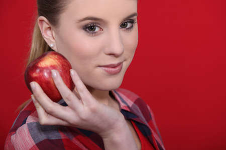Attractive woman holding a red apple Stock Photo - 11457174