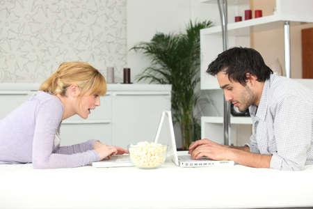 young couple sitting face to face with laptop photo