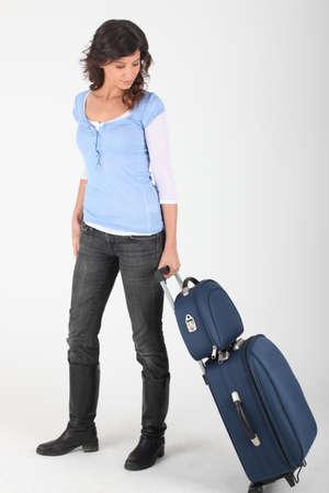 arriving: Woman wheeling luggage Stock Photo