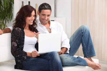 good looking woman: Couple on a sofa with a laptop Stock Photo