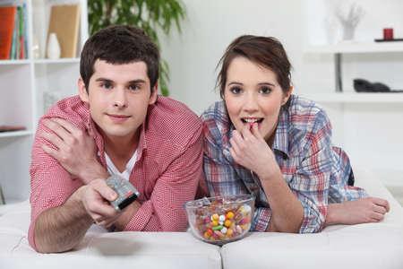 pareja viendo tv: Pareja joven viendo la televisi�n con un mando a distancia y un taz�n de dulces Foto de archivo