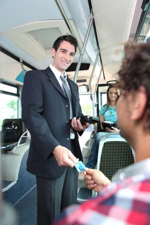 30 34 years: Smiling conductor checking tickets on a tram