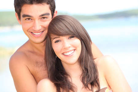 man woman hugging: young couple at the beach Stock Photo