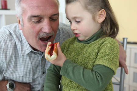Granddaughter giving her grandfather a piece of bread with jam to eat photo