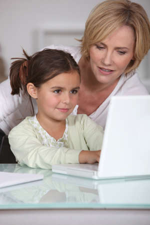 mother showing her little girl how to use the laptop photo