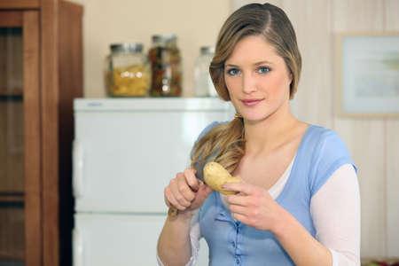 Woman cutting a potato photo