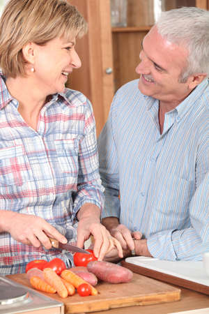 Mature couple preparing vegetables photo