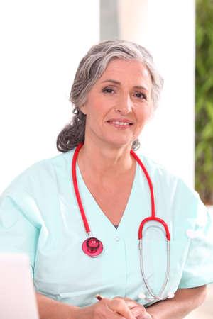 enfermeros: M�dico en matorrales trabajando en un escritorio Foto de archivo
