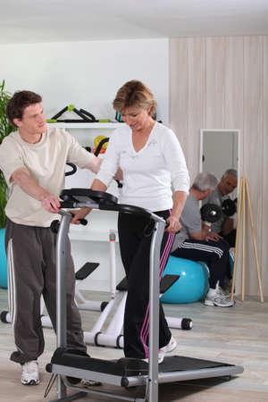 Mature woman using a treadmill photo