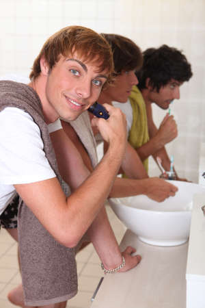 Boys shaving and brushing their teeth photo