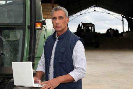 agricultural machine: Farmer with laptop stood by tractor