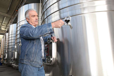Wine producer stood by tanks