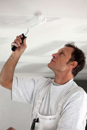 Man painting ceiling white Stock Photo