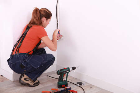 wireman: young woman installing electricity in a house Stock Photo