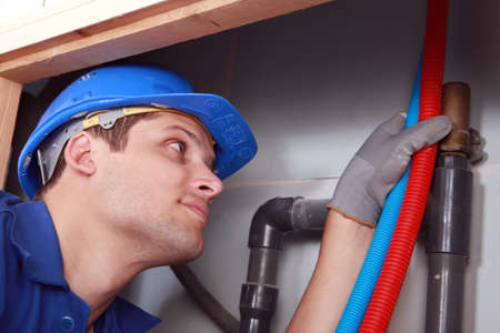 Plumber with hot and cold flexible water pipes photo