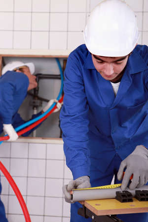 maintenance fitter: Plumber measuring and cutting plastic tube Stock Photo