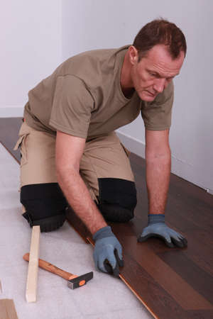 Man laying down flooring photo