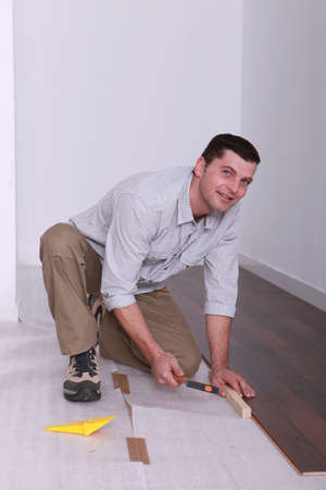 skilled labour: Man laying wooden flooring