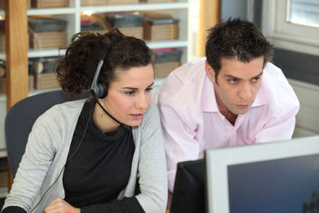 two office colleagues looking at a screen photo