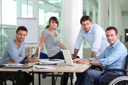 discapacidad: Hombre en silla de ruedas sentado en el escritorio con sus colegas
