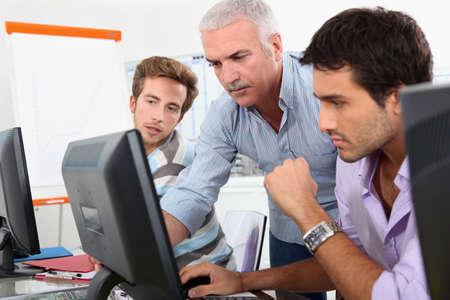 Les élèves plus âgés qui utilisent des ordinateurs dans la salle de classe Banque d'images
