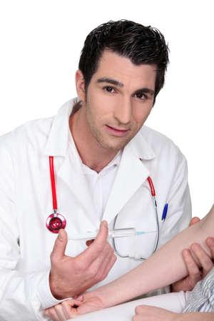 inyeccion intramuscular: Joven médico dar una inyección a un paciente