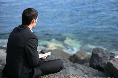 Businessman sat on rock by the sea