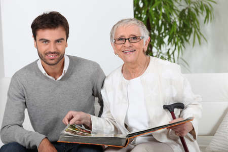 55 60 years: Elderly person looking at photos with son