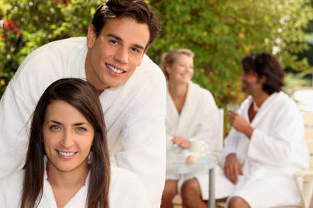 dressing gowns: Two couple sat in garden wearing dressing gowns Stock Photo