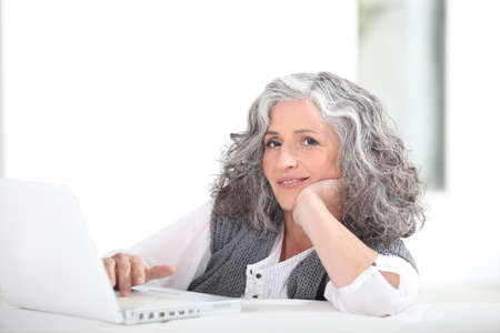 slumped: mature grey-haired lady with laptop Stock Photo