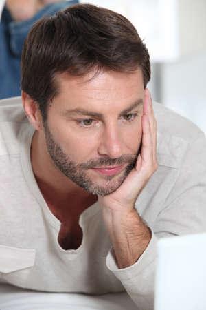 man face close up: Man on laptop Stock Photo