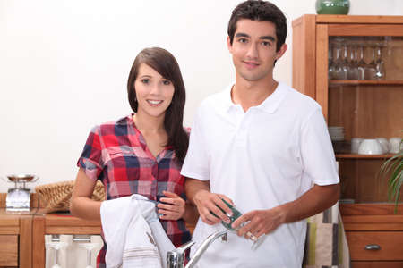 welcome home: young couple wiping glasses in the kitchen