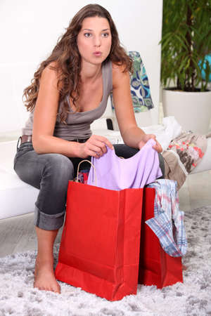 A brunette going through her shopping. Stock Photo - 11455845