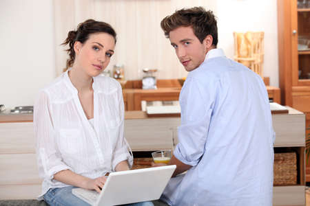 young couple with laptop in the kitchen photo