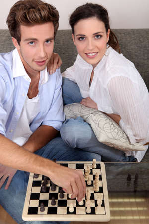 Young couple playing chess photo