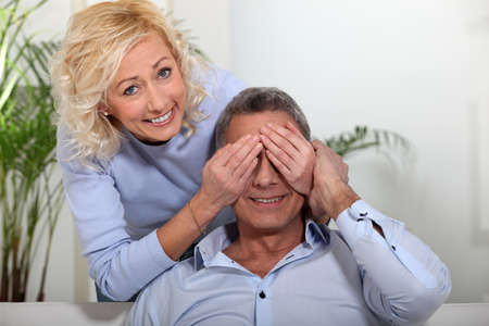 50 55: Woman covering her husband Stock Photo