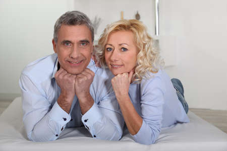 Man and woman lying with their heads propped up on their hands Stock Photo - 11455851