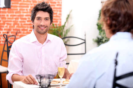 25 to 30: Male couple at restaurant Stock Photo