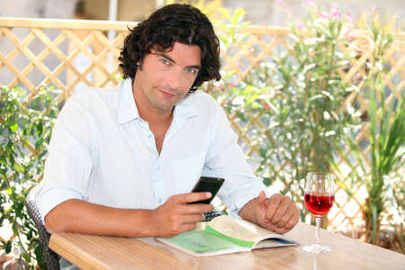 Man sitting at an outdoor cafe table with a cellphone and glass of rose photo