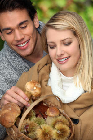 young couple with basket full of mushrooms and chestnuts photo