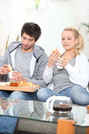 Couple having breakfast on the sofa photo