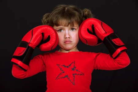 little girl with boxing gloves pulling a face against black background photo