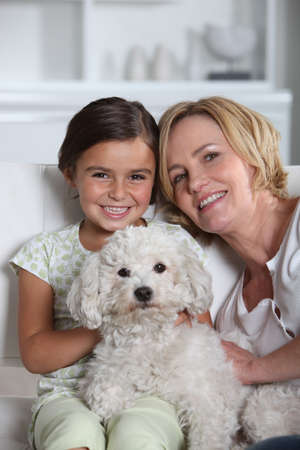 Mother, daughter and white dog sitting in a white living room photo
