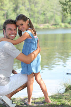 moment: Father and daughter standing on a riverbank