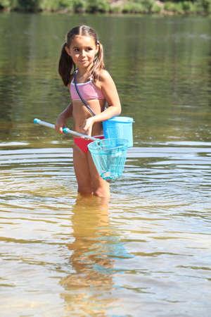 Young girl fishing with a net photo
