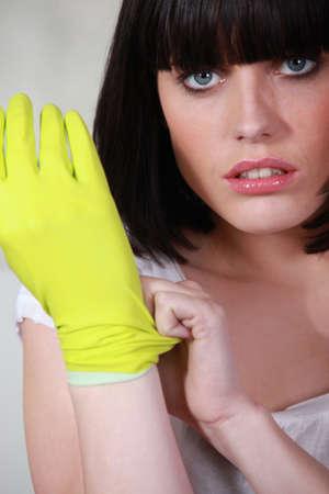 lavar platos: Mujer de ponerse los guantes de goma Foto de archivo