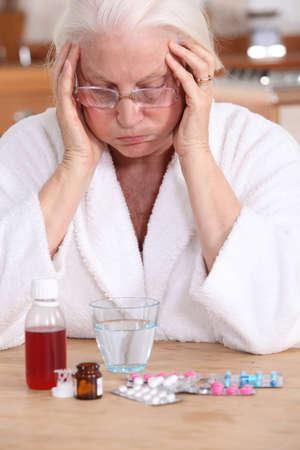 persona deprimida: Anciana con una gran cantidad de medicina que debe tomar
