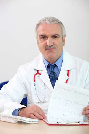 Mature doctor with clipboard and computer photo