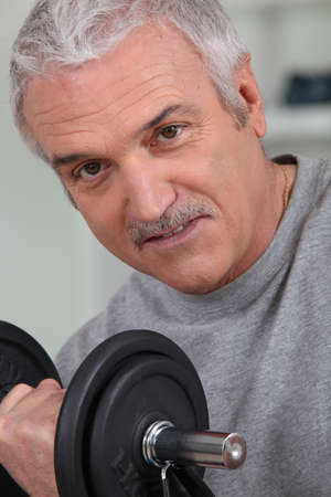 senior man doing exercises with a dumbbell photo